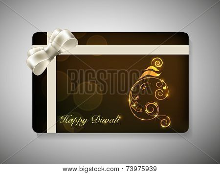 Happy Diwali gift card with Lord Ganesha made by floral design and silver ribbon decoration on brown background.
