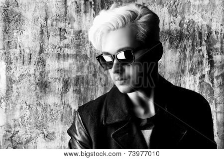 Black-and-white portrait of a fashionable male model with blond hair wearing black jacket and sunglasses. Men's beauty, fashion.