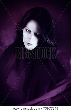 Handsome gothic man over dark background.