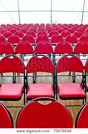 Horizontal rows of red chairs in a public hall