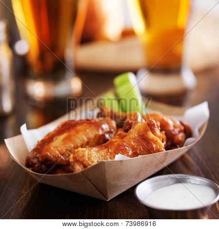 buffalo chicken wings in disposable tray with celery, ranch, and beer