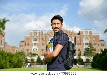 Stock image of university student holding book at college