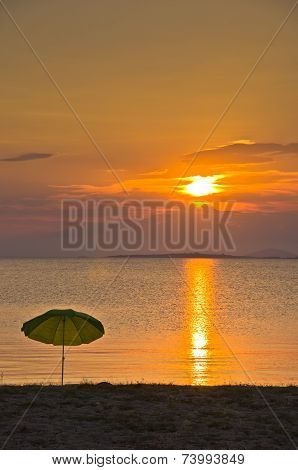 Sunshade on a sandy beach at sunset