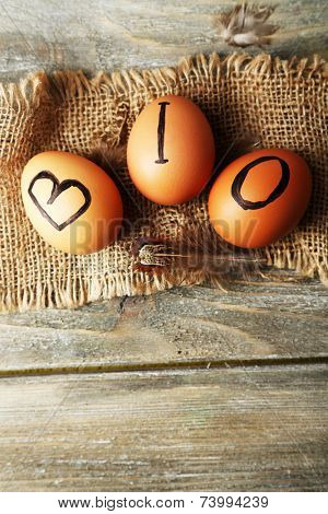 Eggs with inscription BIO on eggshell, on wooden background