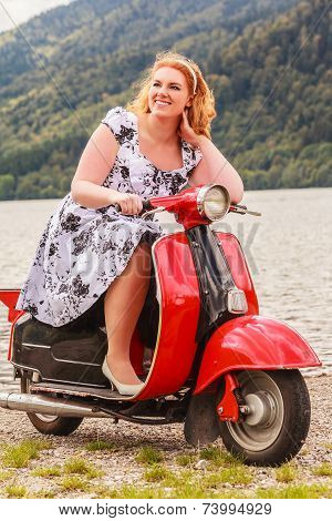Red-haired beauty with overweight on a red scooter
