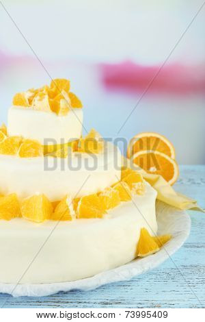 Beautiful wedding cake with oranges on  light background