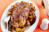 foto of frizzle  - A tasty roast with baked potatoes on a table with a tablecloth orange - JPG