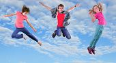 image of cloudy  - Group of happy children exercising jumping and having fun in the bright blue cloudy sky Childhood happiness active lifestyle concept - JPG