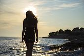 stock photo of darkness  - girl walking by the sea at sunset - JPG