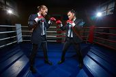 pic of boxing ring  - Professional businessmen in suits and boxing gloves standing opposite one another on boxing ring - JPG