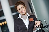 stock photo of front-entry  - Happy female receptionist worker standing at hotel counter with bell - JPG