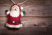 Hand made felt Santa Claus Christmas decoration. Vintage style, over old wood background, with space