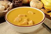 stock photo of butternut  - A bowl of butternut squash soup with croutons and dinner rolls  - JPG
