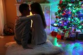 picture of carpet  - Nice love couple sitting on carpet in front of fireplace - JPG