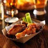 stock photo of sticks  - basket of barbecue buffalo chicken wings with celery sticks and ranch sauce  - JPG