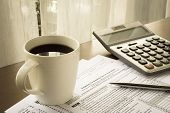 picture of calculator  - Tax forms of expenses for business use of your home place on home office table with a cup of coffee calculator and pen