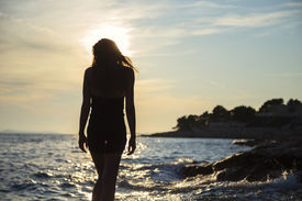 stock photo of wet  - girl walking by the sea at sunset - JPG