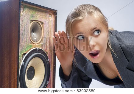 Surprised Caucasian Blond Female Harkens To Outdated Loudspeaker In Studio