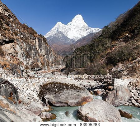 Ama Dablam With Stony And Wooden Bridge Above River