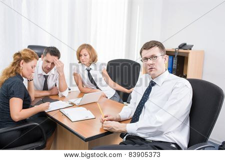 Manager with office workers in board room
