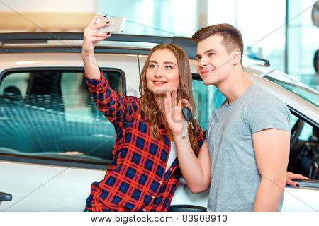 Happy young couple in dealership