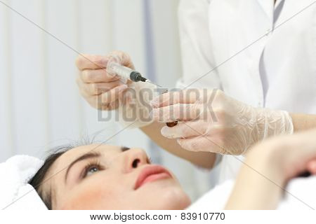 Hand with a syringe over the face, close up.
