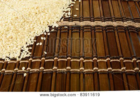 Sesame Seeds Scattered On Brown Mat In The Corner