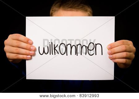 Child Holding Sign With German Word Wilkommen - Welcome