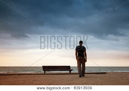 Man Goes To The Sea Near Old Wooden Empty Bench