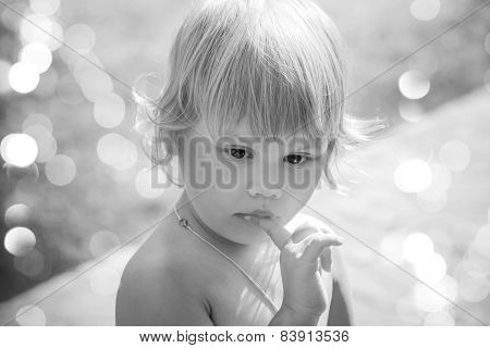 Outdoor Portrait Of Cute Thinking Blond Baby Girl