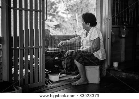 Senior Asian Woman Cooking In Kitchen