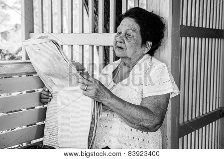 Senior Asian Woman  Relaxing With Newspaper