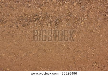 Texture Of Dry Red Clay With Stones Close-up.