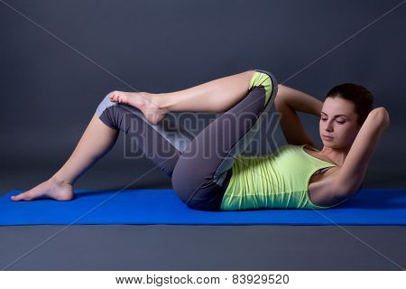 Woman Doing Strength Exercises For Abdominal Muscles Over Grey