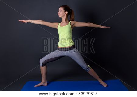 Young Sporty Woman Doing Yoga Over Grey
