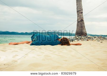 Young Woman Lying Under Palm Tree On Beach