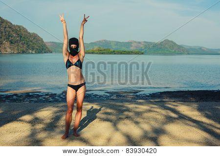 Woman Wearing Bikini And Balaclava On Beach