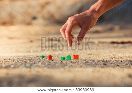 Hand Picking Up Plastic House On Beach