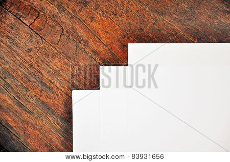 Three sheets of white paper lying on a  wooden  surface