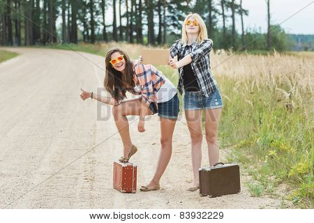 Happy Girls Hitchhike With Cardboard On Road
