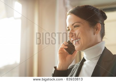 Attractive Woman On The Phone Next To A Window