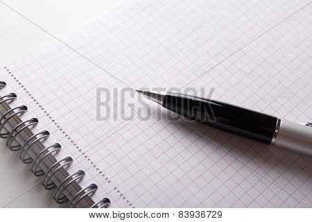 Close Up Of Note Book With Checked Pages And Pen