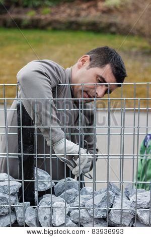 handyman instaling the stone mesh