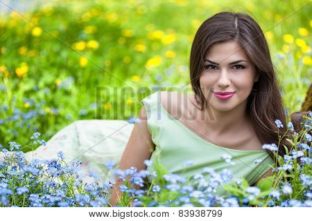 Young woman is lying on field