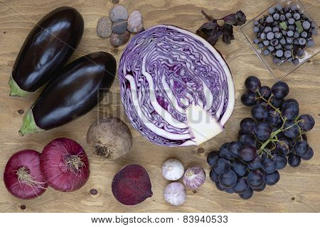 Set of vegetables and berries on aged wooden background.