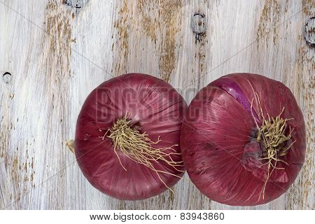 Two red onions on the white painted wooden background.