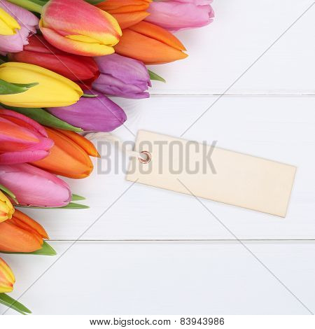 Tulips Flowers In Spring Or Mother's Day With Greeting Card On A Wooden Board