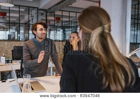 Young Man Explaining New Business Plan To Coworkers