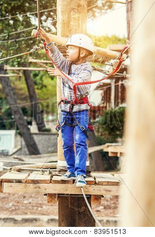 Boy climbing on the ropes in the adrenaline park
