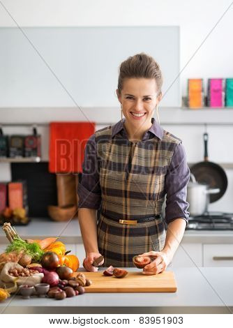 Happy Young Housewife Cutting Cherokee Purple Tomato